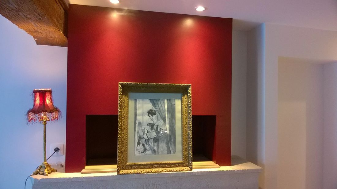 un coin déco avec une belle illustration de Yannick Corboz sur le coin de la cheminée